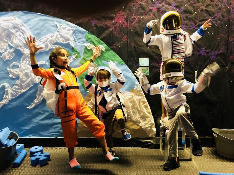Four kids dressed as astronauts play in the PIE room. The wall behind them shows a view of Earth from outer space.